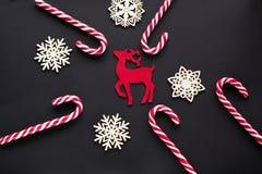Julgodis med röda hjortar, vit snöflinga på svart bakgrund vita röda stjärnor för abstrakt för bakgrundsjul mörk för garnering mo Royaltyfria Bilder