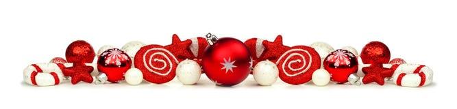 Julgräns av den isolerade röda och vitprydnader och dekoren Arkivfoton