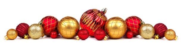 Julgräns av röda och guldprydnader som isoleras på vit Arkivfoton
