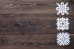 Julgräns - träbakgrund med snöflingor Arkivbild