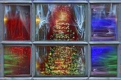 Julgran bak fönstret arkivfoto