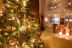 Julgran dekorerad pepparkaka, kanel och bollnärbild ljus från girlanderna royaltyfri foto