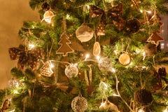 Julgran dekorerad pepparkaka, kanel och bollnärbild ljus från girlanderna Royaltyfria Bilder