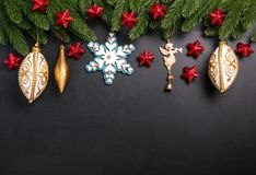 Julgran förgrena sig med garneringar på en svart bakgrund arkivbild
