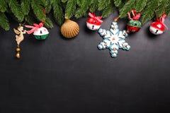 Julgran förgrena sig med garneringar på en svart bakgrund arkivbilder