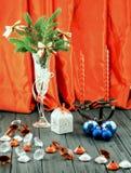 Julgran i den vita dekorativa bägaren, den vita gåvaasken, blåttbollar, ljusstake med röda stearinljus och dekorativa stenar Arkivbild