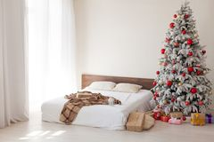 Julgran i ett vitt sovrum med sänginre av gåvor för nytt år royaltyfri foto