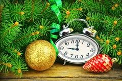 Julgran, klockor, leksaker och träbakgrund. Arkivfoton