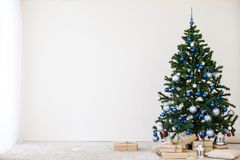 Julgran med blått i ett vitt rum med leksaker för jul Royaltyfri Foto