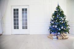 Julgran med blått i ett vitt rum med leksaker för jul Royaltyfria Bilder