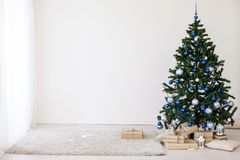 Julgran med blått i ett vitt rum med leksaker för jul royaltyfri fotografi