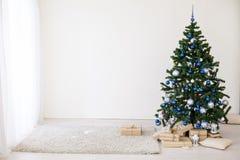 Julgran med blått i ett vitt rum med leksaker för jul Fotografering för Bildbyråer