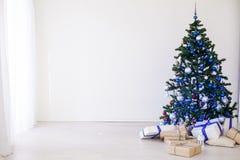 Julgran med blått i ett vitt rum med leksaker för jul royaltyfria foton