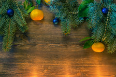 Julgran med blåttbollar och mandarines i levande ljus arkivfoto