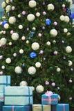 Julgran med bollar och gåvaaskar arkivfoto
