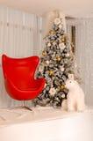 Julgran med den röda fåtöljen och en isbjörn i interioen Arkivbild