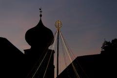 Julgran med en blixtkedja med en konturkloster i baclgrounden Arkivbild