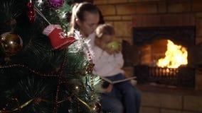 Julgran med familjläseboken nära spisen på bakgrunden arkivfilmer