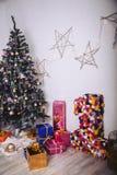 Julgran med gåvaaskar och dekorativa beståndsdelar i rummet Arkivbild