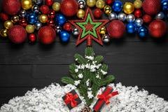Julgran med gåvaasken och snö Julgarnering på svart träbakgrund royaltyfri bild