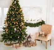Julgran med gåvor i vardagsrummet Arkivbilder