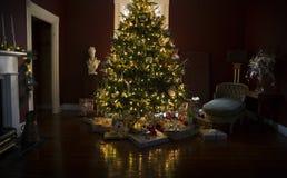 Julgran med gåvor och ljus Arkivfoto