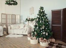 Julgran med gåvor under i vardagsrum Arkivbilder
