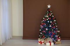 Julgran med girlander på bruna vita gåvor för nytt år för bakgrund Royaltyfria Foton