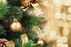 Julgran med guld- suddig ljus bakgrund arkivfoto
