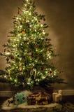 Julgran med härliga ljus, garnering, leksaker och gåvor arkivfoton