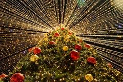 Julgran med kulöra bollar och glödande ljus nytt år arkivbilder