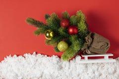 Julgran med leksaker på en släde i dekorativ snö Julberättelse på pappers- röd bakgrund arkivfoton