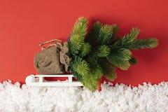 Julgran med leksaker på en släde i dekorativ snö Julberättelse på pappers- röd bakgrund royaltyfria bilder