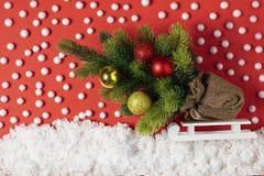 Julgran med leksaker på en släde i dekorativ snö med snöflingor Julberättelse på pappers- röd bakgrund royaltyfri bild
