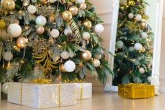 Julgran med ljusa bollar och garneringar för grankottar och gåvor under den i inre nytt år 2019 December royaltyfri bild
