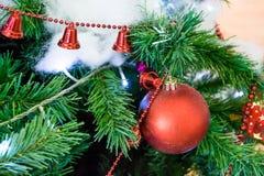 Julgran med röda skinande leksaker och bomull som snö Arkivbilder