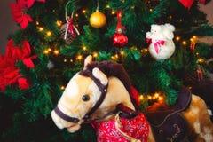 Julgran med struntsakgarneringar och felika ljus med en vagga häst för leksak royaltyfria foton