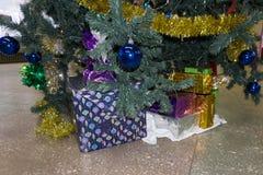 Julgran med trälantliga garneringar och gåvor under den i vindinre arkivbilder