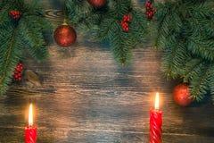 Julgran med två stearinljus och röda bollar fotografering för bildbyråer