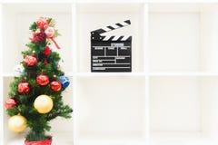 Julgran och filmclapper på den tomma vita bokhyllan fotografering för bildbyråer