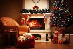 Julgran- och julgåvaaskar i inre med en spis royaltyfri bild