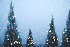 Julgran- och ljusbokeh med snöfall på himmelbakgrund i vinter Arkivbild