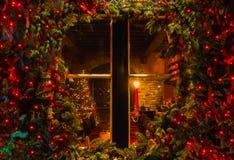 Julgran och spis som ses till och med ett träkabinfönster arkivfoton