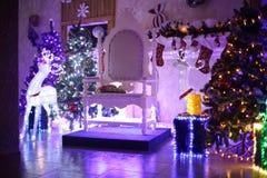 Julgran och stol för Santa Claus i en hemtrevlig vardagsrum royaltyfri bild