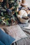 Julgran på golv med kuddar på en grå matta i den vita inre Julgranen dekorerar med konstgjort Arkivbild