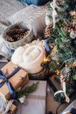 Julgran på golv med kuddar på en grå matta i den vita inre Julgranen dekorerar med konstgjort Arkivbilder