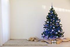Julgran på juldag i ett vitt rum med gåvor Arkivfoton