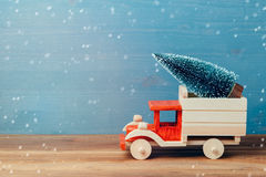 Julgran på leksaklastbilbilen på trätabellen Begrepp för julferieberöm arkivbild