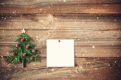 Julgran på träbräde med en klibbig anmärkning fotografering för bildbyråer