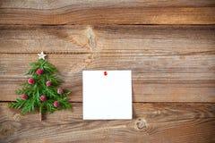Julgran på träbräde med en klibbig anmärkning royaltyfria foton
